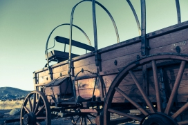 The old wagons are lined up facing west into the sunset.