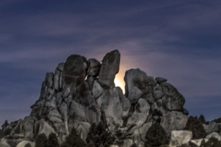 Moon rising behind a huge boulder.