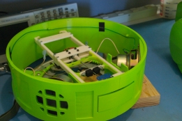 The 3d printed R2D2 is filled with sensors, wires, and motors. This section houses the speakers and electronics for a sliding tray mechanism.