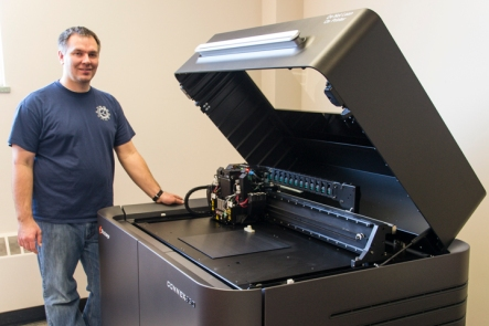 Geran stands next to the big 3d printer. This machine can print in multiple materials, and can blend stiff and flexible materials for desired properties.