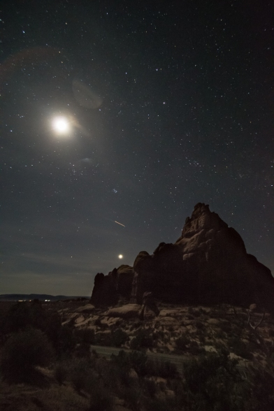 Moon stars and airplanes behind a giant boulder in the desert