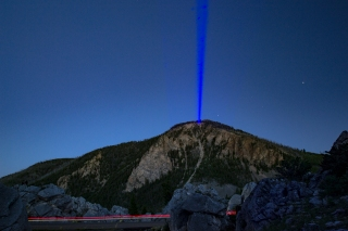 Shining my blue lazer at the mountain top as a car drives through the scene in Yellowstone National Park